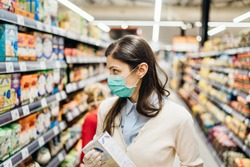 Shopper with mask safely shopping for groceries due to coronavirus pandemic in stocked grocery store.COVID-19 food buying.Non perishable food.Full grain carbs.Rice shortage.Lockdown preparation