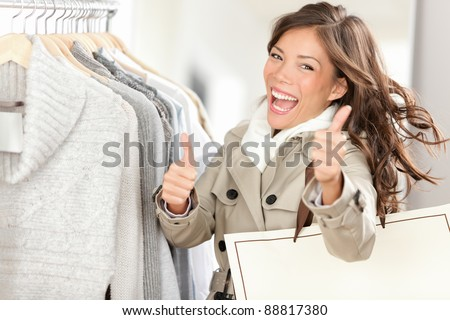 Shopper woman happy shopping and buying clothes. Joyful excited smiling woman. mixed race Caucasian / Chinese Asian female model holding shopping bags in coat inside in clothing store giving thumbs up