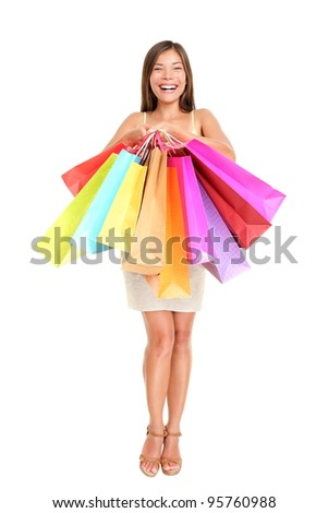 Shopper woman holding shopping bags standing happy smiling and excited in full body isolated on white background. Beautiful multiracial Chinese Asian / Caucasian female model joyful.