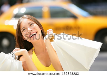 Shopper woman shopping in New York City, Manhattan, USA. Shopper girl holding shopping bags smiling happy with yellow taxi cab in background. Young multiracial Asian Caucasian female model in dress.