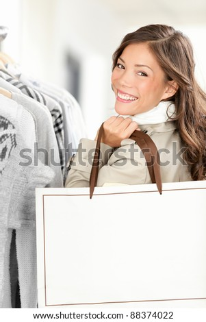 Shopper woman showing shopping bag with copy space. Smiling Caucasian / Chinese Asian female model buying clothes in clothing store.