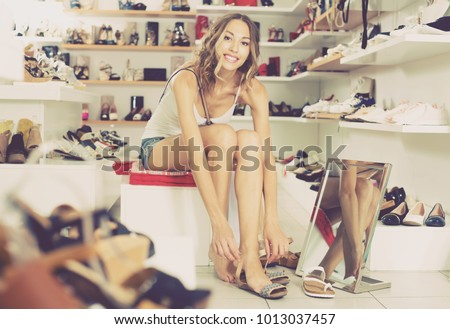 shopper 20-23 years old is trying on summer shoes in boutique. #1013037457