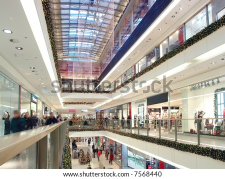 Shoppers doing christmas shopping in big shopping center decorated with christmas ornaments and lights