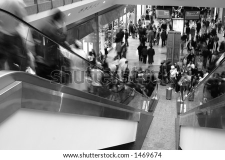 Shoppers rushing around in shopping mall.