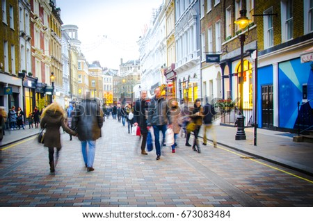Shoppers walk down busy central London High Street  #673083484
