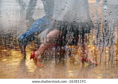 Shoppers walking in rain taken through glass window