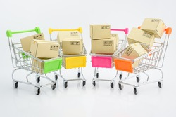 Shopping addiction, shopping lover or shopaholic concept : Paper boxes / cartons and small toy shopping cart, on white background. Many people / consumers or buyers addicted to buy unnecessary things.