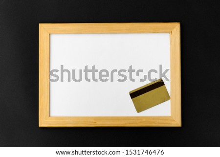 shopping and consumerism concept - white magnetic board and credit card on black background