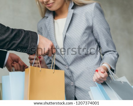 shopping and consumerism. woman is curious what's in man's bags.