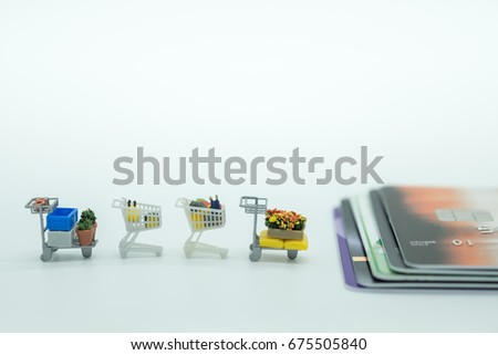 Shopping and e-commerce concept. Close up of four miniature shopping carts toy figure row with stack of credit cards with copy space