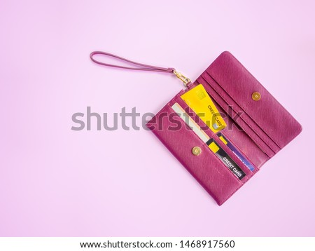 shopping and payment concept from red clutch purse on pink background with credit cards and discount cards in it. Closeup of modern red leather wallet. Top view on the wallet. Сток-фото ©