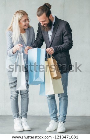 shopping and surprise for a loved one. woman showing purchase to a man holding multiple bags.