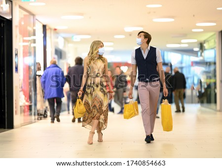 Shopping at the time of Corona Virus. Handsome young and fashion couple at the shop center walking with protective surgical face mask, shopping bags in hand and looking at shop windows. Alert Covid-19
