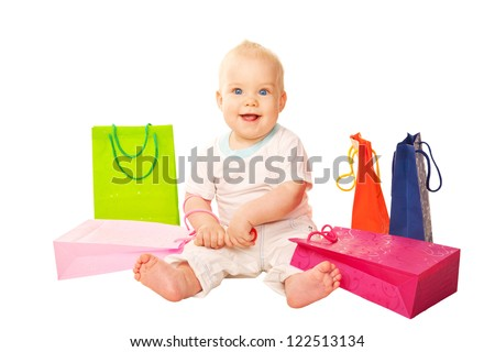 Shopping baby. Happy smiling kid sitting with shopping bags. Isolated on white background