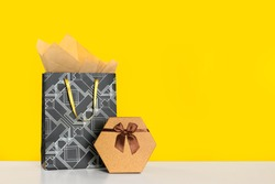 Shopping bag and gift box on yellow background. Space for text