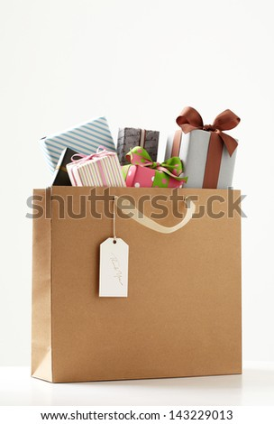 Shopping Bag of presents on white table.  brown Shopping bag.