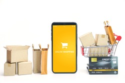 Shopping bags and paper cartons or parcel in cart with credit card and smart phone. Shopping service on online web and offers home delivery.  online shopping concept.