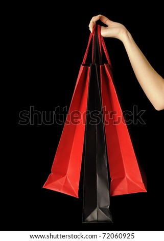Shopping bags held by a woman, over black background