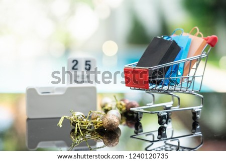 Shopping bags in shopping cart and calendar on date 25 December isolated on white background. Concept of Black Friday, boxing day, year end sales.