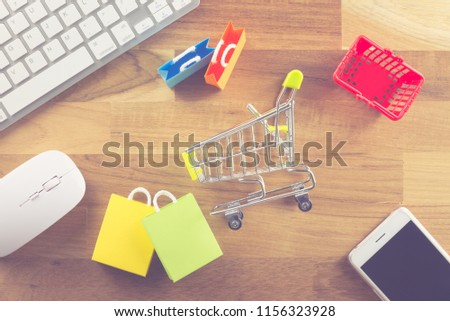 Shopping bags, supermarket cart, grocery basket, smart phone, keyboard and mouse computer on wooden background. Worldwide online shopping b2c e-commerce on internet website or social media at home.