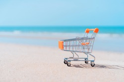 Shopping basket cart on sand beach with blue sky background. Summer sale and business service concept. Vintage tone filter effect color style.