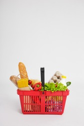 shopping basket full of healthy food over white background with copy space