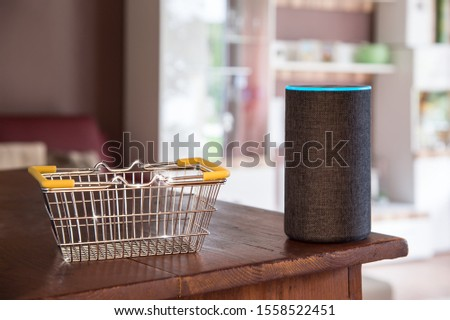 Shopping basket is filled virtually. The smart speaker buys goods from the Internet by voice command. The shopping cart glistens and sparkles in the living room