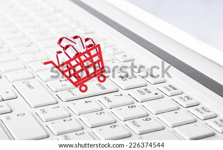 Shopping basket with gift boxes on computer keyboard  as online shopping concept
