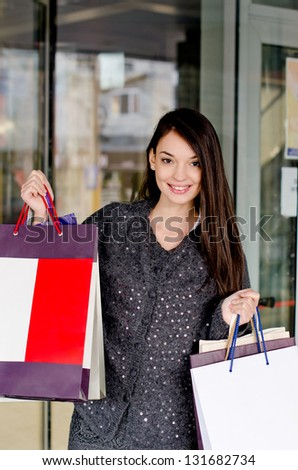 Shopping. Beautiful girl holding many shopping bags in front of the mall.