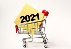 Shopping cart and text numbers 2021 on white paper note list. Shopping list, business concept on white background.