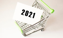 Shopping cart and text 2021 on white paper. Shopping list concept on light background.