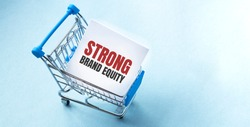 Shopping cart and text STRONG BRAND EQUITY on white paper note list. Shopping list concept on blue background.