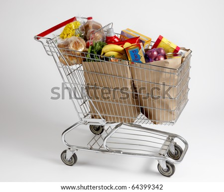 Shopping cart filled with bagged groceries shot on white with soft shadows