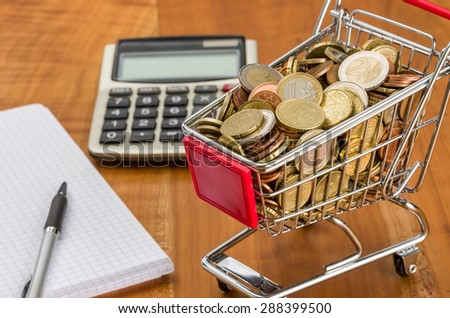 Shopping cart filled with coins on a wooden desk