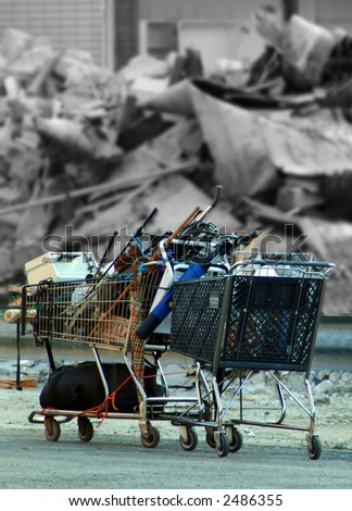 Shopping cart filled with recyclables in front of demolished building