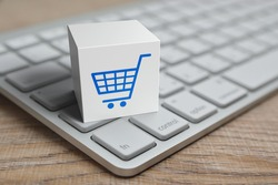 Shopping cart flat icon on white block cube with modern computer keyboard on wooden table, Business shop online concept