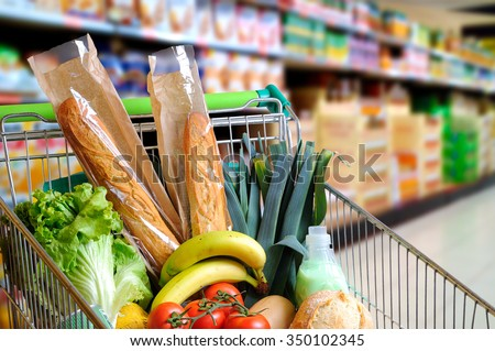 Shopping cart full of food in the supermarket aisle. High internal view. Horizontal composition