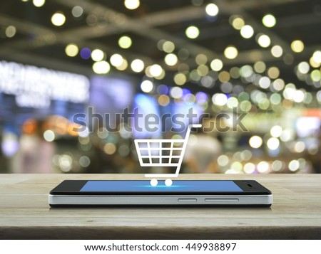 Shopping cart icon on modern smart phone screen on wooden table in front of blur light and shadow of shopping mall, Shop online concept