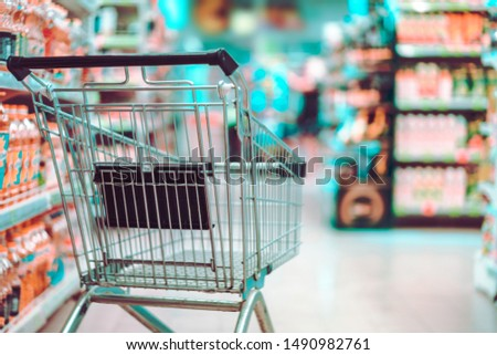 Shopping cart in supermarket aisle. Buying food in grocery store.
