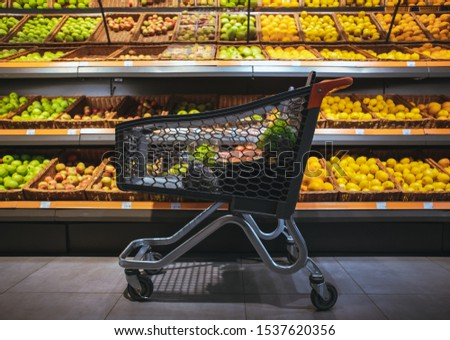 shopping cart in the middle of the picture shelf with oranges and apples on background