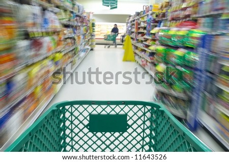 Shopping cart moving through aisle of supermarket
