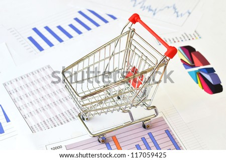 Shopping cart on a financial report - stock photo