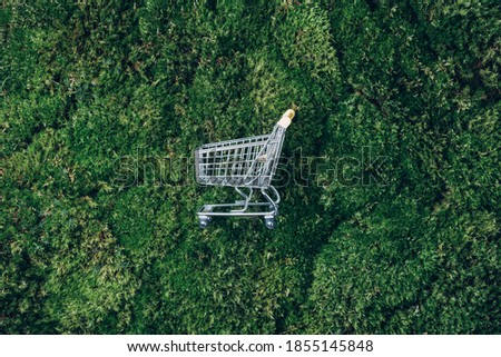 Shopping cart on green grass, moss background. Top view. Minimalism style. Creative design. Shop trolley. Sale, discount, shopaholism, ecology concept. Sustainable lifestyle, conscious consumption.