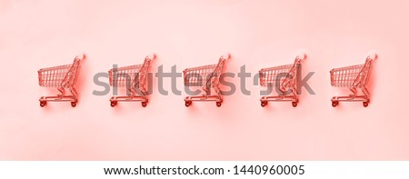 Shopping cart on trendy coral color background. Minimalism style. Creative design. Shop trolley at supermarket. Sale, discount, shopaholism concept. Consumer society trend.