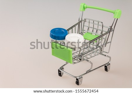 shopping cart shopping cart filled with various containers and packages with modern soft contact lenses, the problem of choosing lenses, variety when buying #1555672454