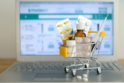 Shopping cart toy with medicaments in front of laptop screen with pharmacy web site on it. Pills, blister packs, medical bottles, thermometer set. Health care and internet shopping.