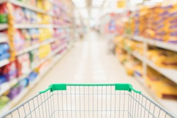 Shopping cart with abstract blur supermarket discount store aisle and pet food product shelves interior defocused background