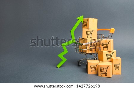 Shopping cart with cardboard boxes with a pattern of trading carts and a green up arrow. Increase the pace of sales, production of goods. Improving consumer sentiment. Strategy for increasing revenue #1427726198