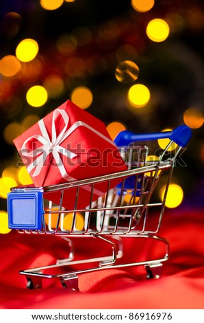 shopping cart with decorative gift box against blurred lights on christmas tree