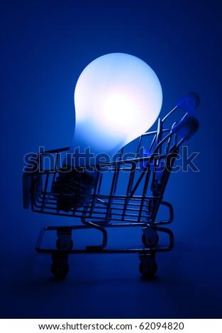 Shopping cart with light bulb in dark blue light.